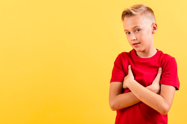 Young boy holding with arms crossed Free Photo