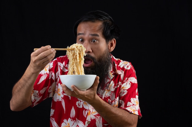 Young boy is feeling surprise with how delicious instant noodle is. young boy is enjoy eatting instant noodle at home. Free Photo