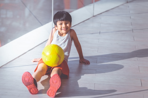 Young boy is sitting with soccer and smiling Premium Photo