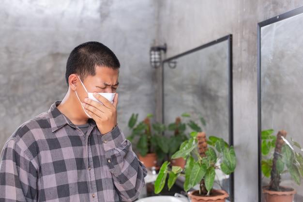 若い男の子は、保護マスクに警告し、トイレでウイルスを保護するために手で口を閉じています。-コンセプトマスクキャンペーン。 無料写真