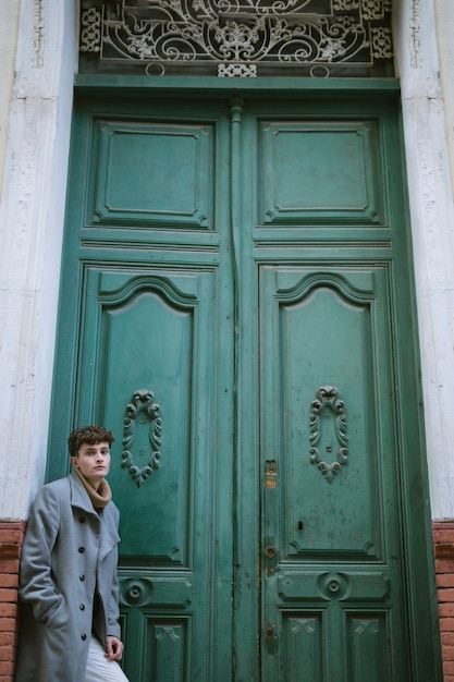 Young boy near a big front door Free Photo