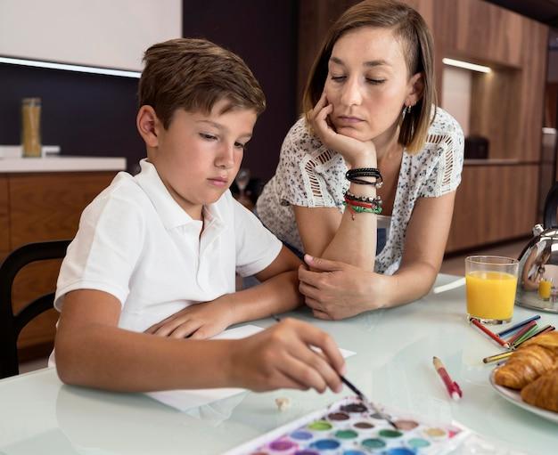 Pittura del giovane ragazzo mentre sua madre sta controllando Foto Gratuite