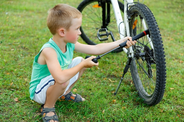 Young boy pumping the bicycle tube Premium Photo