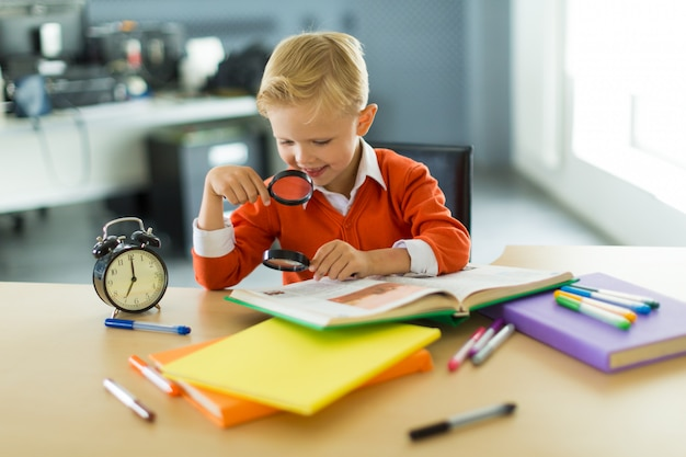 Young boy sit at the desk in the office, hold magnifier Premium Photo