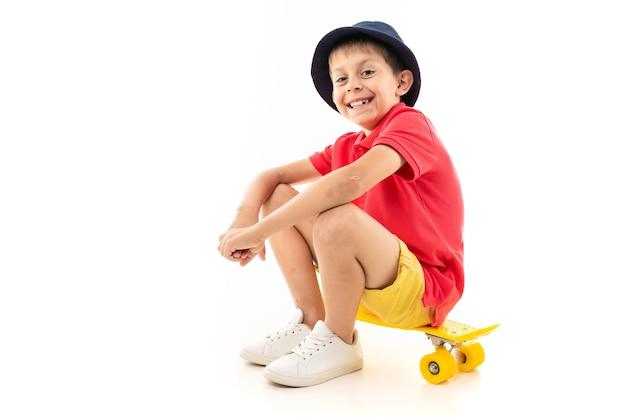 黄色いスケートボードに座っている少年 Premium写真