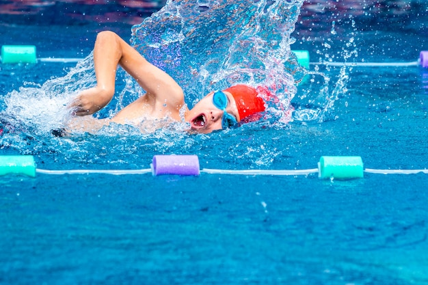 Young boy swimmer practicing his freestyle stroke in a local swimming pool Premium Photo