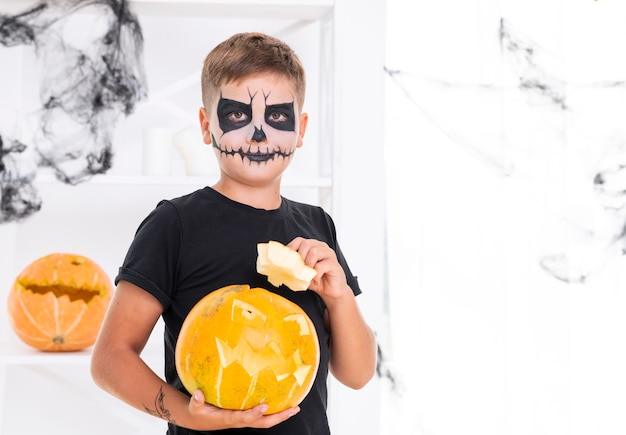 Young boy with face painted holding a pumpkin Free Photo