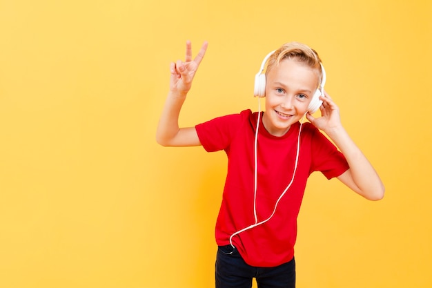 Young boy with headphones listening music Free Photo