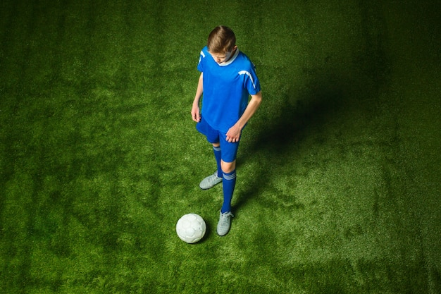 Young boy with soccer ball doing flying kick Free Photo