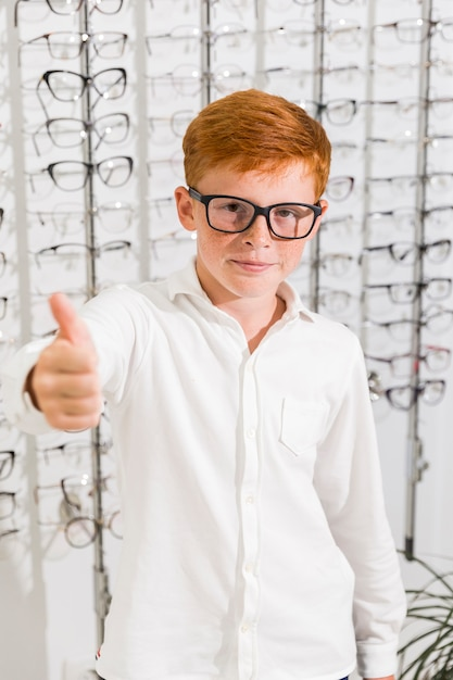 Young boy with spectacle showing thumb up gesture in optics store Free Photo