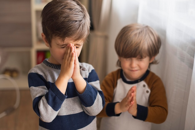Young boys praying together at home Free Photo