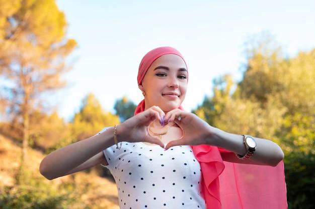 心の手のシンボルを保持している若い乳がん生存者 Premium写真