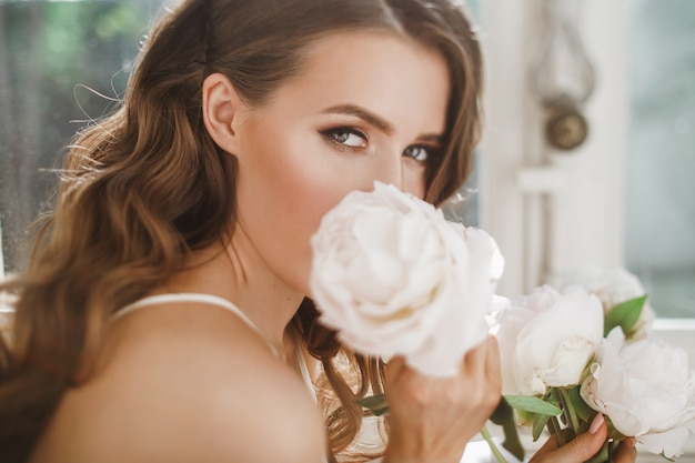Young bride holds a bouquet of peonies siting on the windowsill in the bright morning Free Photo