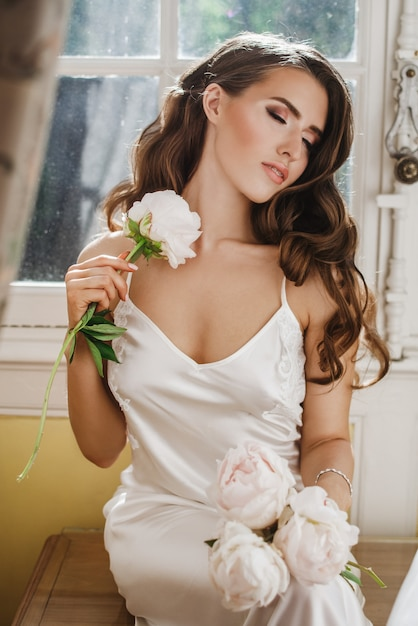 Young bride holds a bouuqet of peonies siting on the windowsill in the bright morning Free Photo