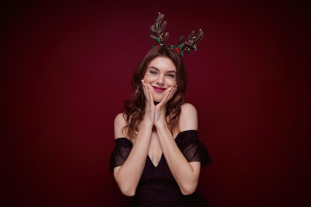 Young brown haired attractive female wearing evening makeup during chrismas party, holding her cheeks with raised palms and having fun Free Photo