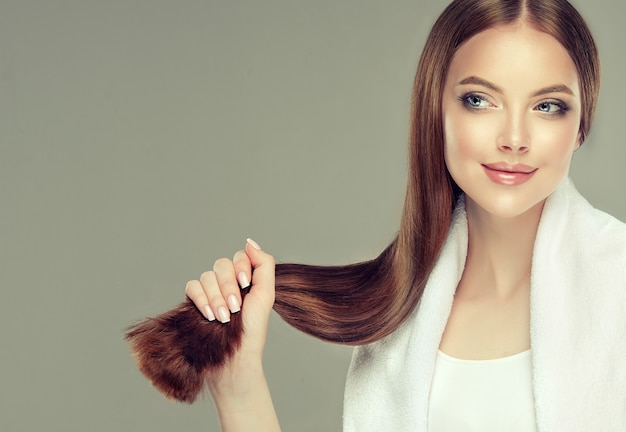 Young, brown haired beautiful model with long, straight hair is holding tail of well groomed and healthy hair in the hand. hair care natural beauty and health. Premium Photo