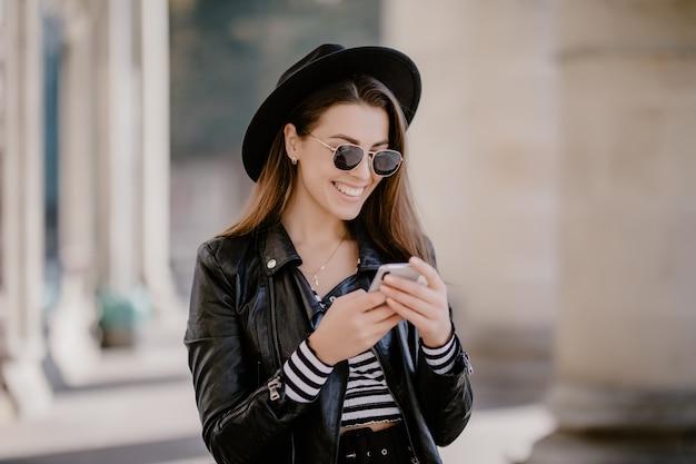 Молодая шатенка в кожаной куртке, черной шляпе на городской набережной и играет на мобильном телефоне Бесплатные Фотографии