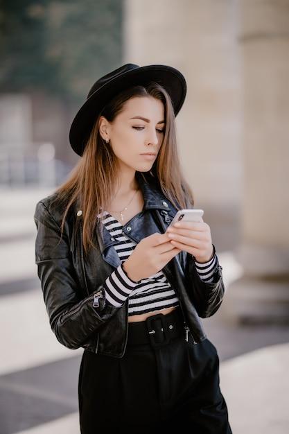 革のジャケット、街の遊歩道の黒い帽子、携帯電話で遊ぶ茶色の髪の少女 無料写真