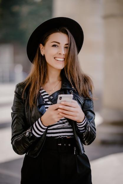 革のジャケット、携帯電話でポーズをとって街の遊歩道の黒い帽子の若い茶色の髪の少女 無料写真