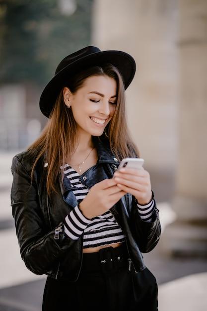 革のジャケット、街の遊歩道の黒い帽子の若い茶色の髪の少女 無料写真