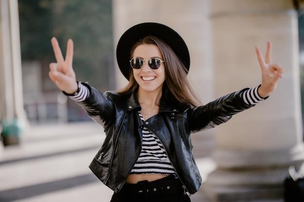 Giovane ragazza dai capelli castani in una giacca di pelle, cappello nero sul lungomare della città Foto Gratuite