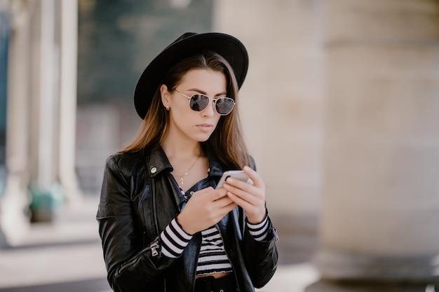 Giovane ragazza dai capelli castani in una giacca di pelle e occhiali, cappello nero sul lungomare della città Foto Gratuite