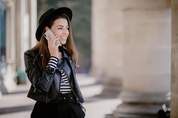 Giovane donna dai capelli castani in una giacca di pelle, cappello nero sul lungomare della città ha una conversazione telefonica Foto Gratuite