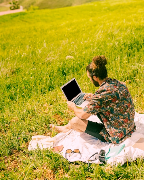 Young brunet man holding laptop on nature Free Photo
