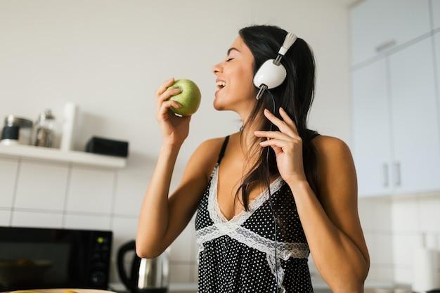 若いブルネットの魅力的な女性は、朝のキッチンで料理、青リンゴを食べる、笑顔、幸せな気分、前向きな主婦、健康的なライフスタイル、ヘッドフォンで音楽を聴く、噛む 無料写真