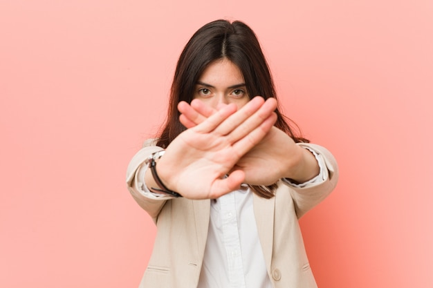 Young brunette business woman against a pink  doing a denial gesture Premium Photo