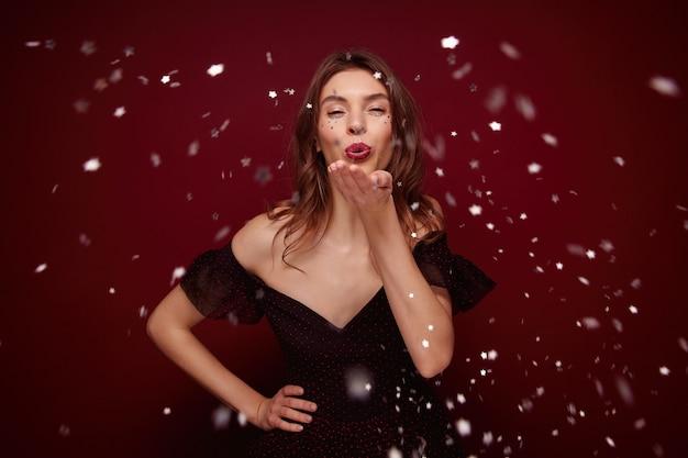 Молодая брюнетка, одетая в элегантное платье, наслаждается новогодней тематической вечеринкой, позируя, поднимая ладонь и дуя серебряное конфетти Бесплатные Фотографии