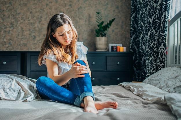 Молодая брюнетка в белой блузке и синих джинсах сидит на кровати в своей комнате, сжимая больное колено Premium Фотографии