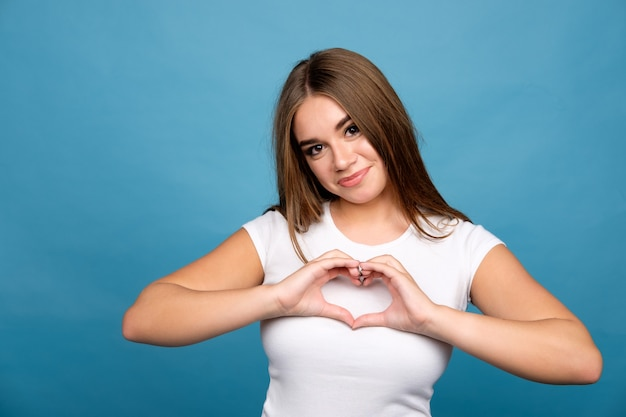 Young brunette girl in white t-shirt showing hear sign using hands, blue background Premium Photo