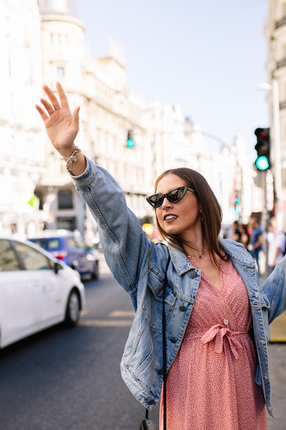 Young brunette woman asking for a taxi raising her arms in madrid city. fashion model wearing pink dress, denim jacket, boots and eye cat sunglasses. female calling a taxi. transportation . Premium Photo