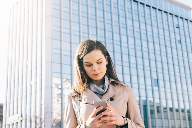 Young brunette woman in beige coat looks at mobile phone on high-rise building background Premium Photo