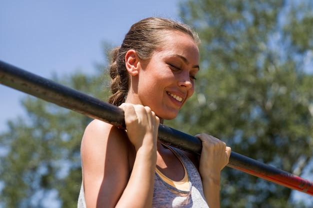 夏の日にスポーツの鉄棒でプルアップを行う若いブルネットの女性 Premium写真