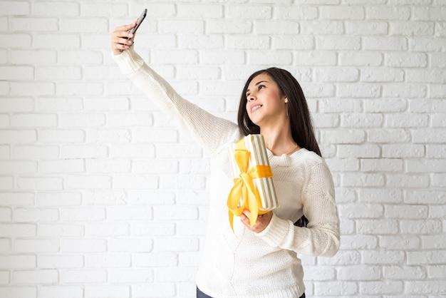 ギフトボックスを保持し、selfieを取る若いブルネットの女性 Premium写真