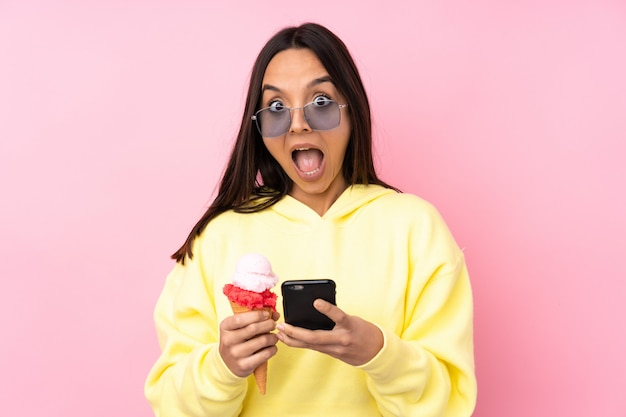 Young brunette woman holding a cornet ice cream over isolated pink wall surprised and sending a message Premium Photo