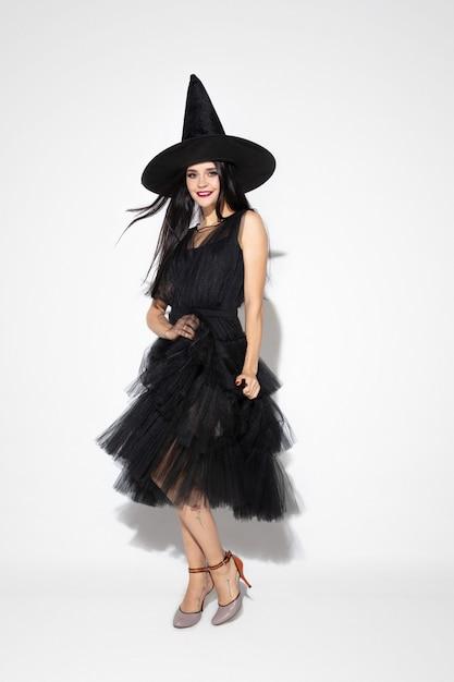 Молодая женщина брюнет в черной шляпе и костюме на белой предпосылке. привлекательная кавказская женская модель. хэллоуин, черная пятница, киберпонедельник, распродажи, осенняя концепция. copyspace. танцы, позирование. Бесплатные Фотографии
