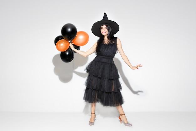 Молодая женщина брюнет в черной шляпе и костюме на белой предпосылке. привлекательная кавказская женская модель. хэллоуин, черная пятница, киберпонедельник, распродажи, осенняя концепция. copyspace. держит воздушные шары, улыбается. Бесплатные Фотографии