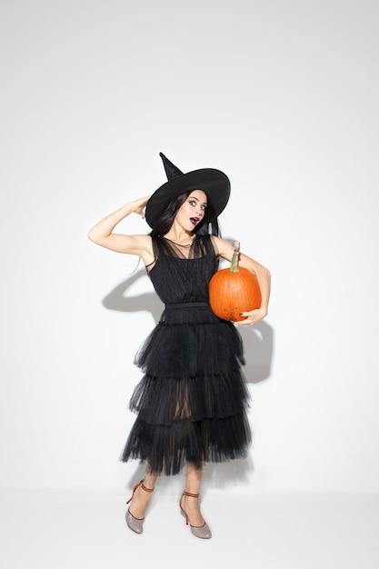 Молодая женщина брюнет в черной шляпе и костюме на белой предпосылке. привлекательная кавказская женская модель. хэллоуин, черная пятница, киберпонедельник, распродажи, осенняя концепция. copyspace. держит накачку. Бесплатные Фотографии