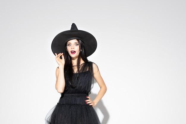 Молодая женщина брюнет в черной шляпе и костюме на белой предпосылке. привлекательная кавказская женская модель. хэллоуин, черная пятница, киберпонедельник, распродажи, осенняя концепция. copyspace. указывая вверх. Бесплатные Фотографии