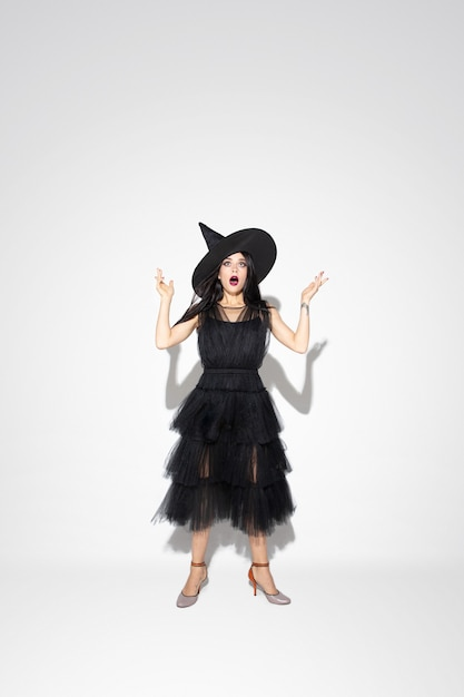 Молодая женщина брюнет в черной шляпе и костюме на белой предпосылке. привлекательная кавказская женская модель. хэллоуин, черная пятница, киберпонедельник, распродажи, осенняя концепция. copyspace. шокирован, изумлен. Бесплатные Фотографии