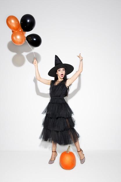 黒い帽子と白い背景の上の衣装で若いブルネットの女性。魅力的な白人女性モデル。ハロウィーン、ブラックフライデー、サイバーマンデー、販売、秋のコンセプト 無料写真