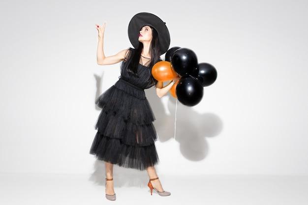 검은 모자와 흰색 바탕에 의상에서 젊은 갈색 머리 여자. 매력적인 백인 여성 모델. 할로윈, 검은 금요일, 사이버 월요일, 판매, 가을 개념 무료 사진