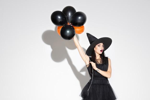 검은 모자와 흰색 의상에서 젊은 갈색 머리 여자 무료 사진