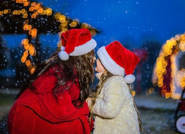 Молодая брюнетка женщина в красной шубе и шапке санта-клауса, целуя молодая дочь в бежевое пальто и шапку санта-клауса. снежный фон. Premium Фотографии