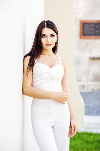 Молодая брюнетка женщина в белых одеждах. Premium Фотографии
