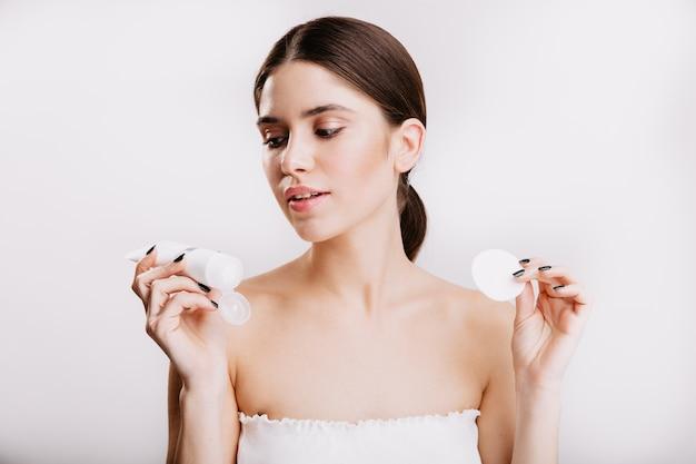 Молодая брюнетка женщина в белом топе смотрит на увлажняющий крем для лица. портрет модели позирует на изолированной стене. Бесплатные Фотографии