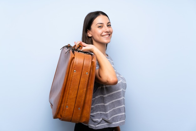 Young brunette woman over isolated blue wall holding a vintage briefcase Premium Photo
